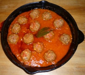 Lamb meatballs stuffed with pine-nuts and baked in tomato sauce